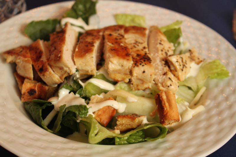 Grilled chicken over a salad with ranch dressing on a white plate