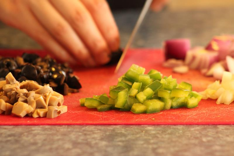 Red cutting board with cut up vegetables and a knife cutting olives