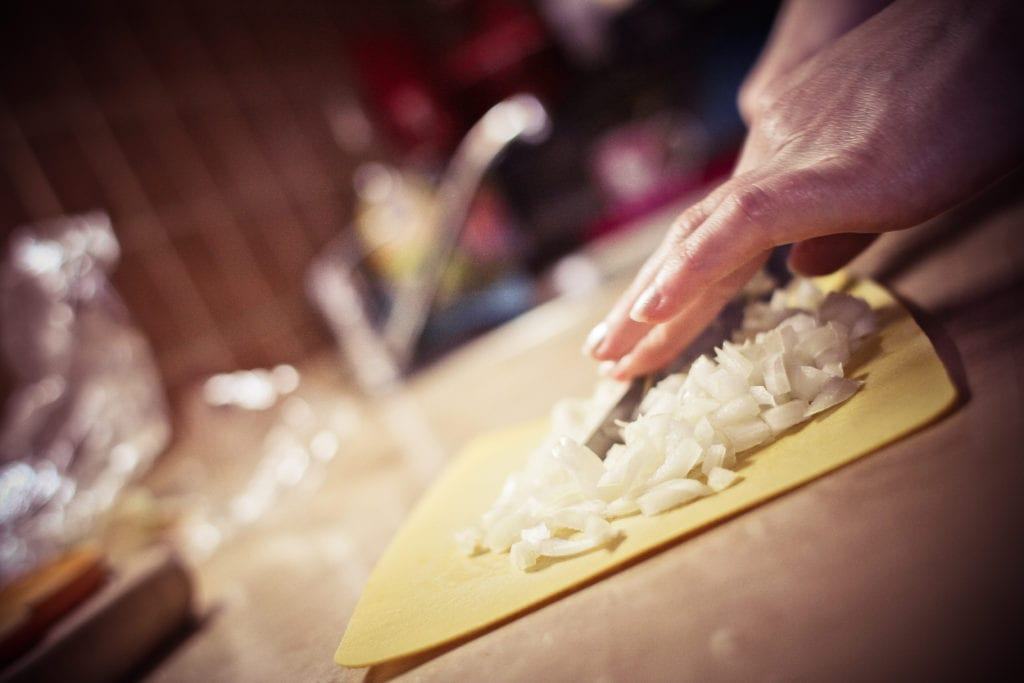 Yellow cutting board on a counter with diced onions