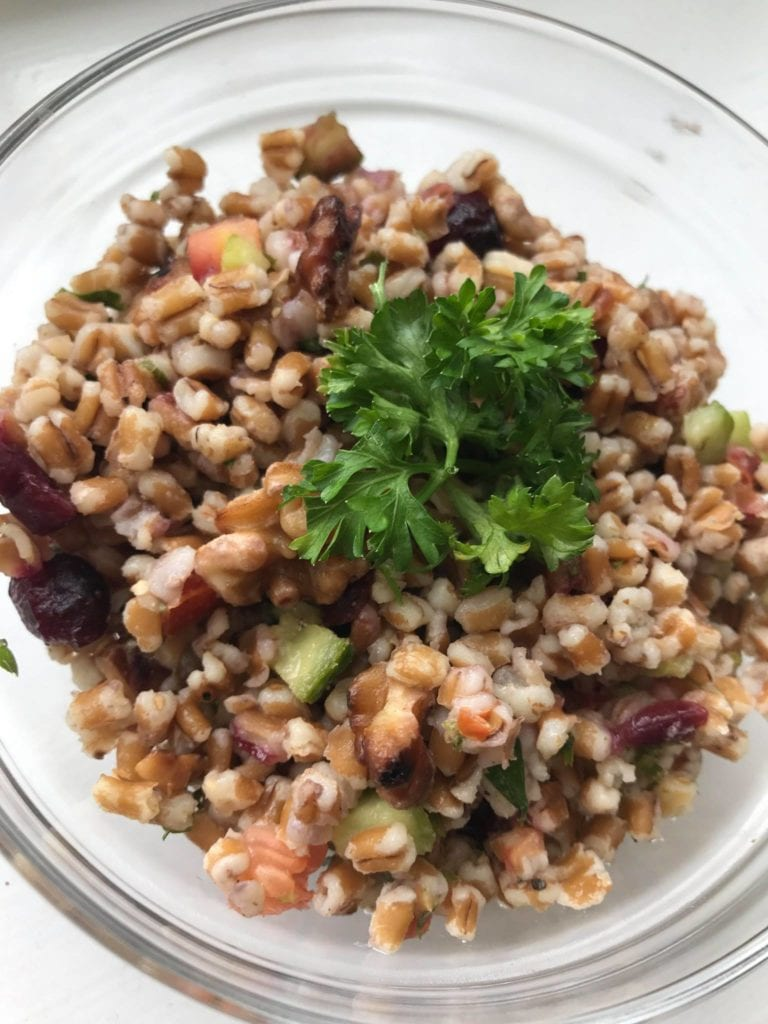 A bowl of wheat berry salad garnished with parsley