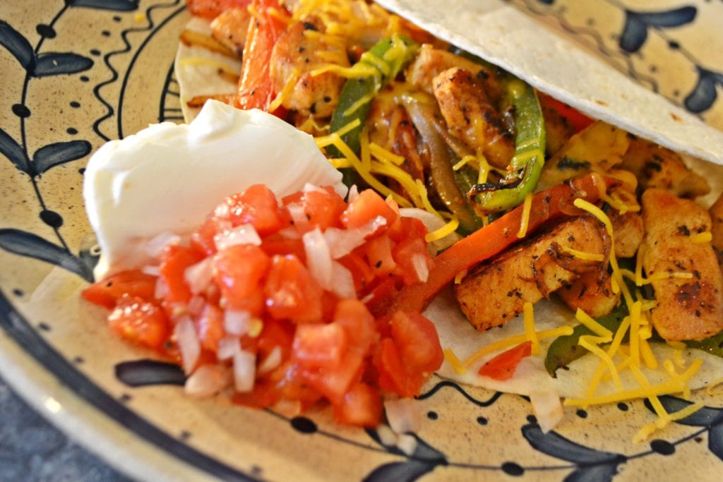 Fajita on a plate with a side of sour cream and salsa