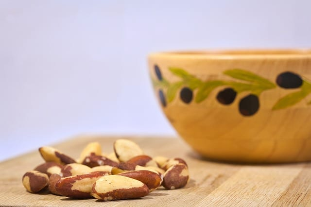 Nuts on a wooden board near a decorated bowl.