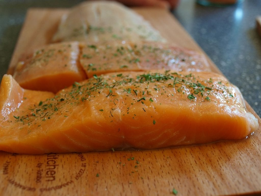 Raw seasoned salmon fillets on wooden cutting board