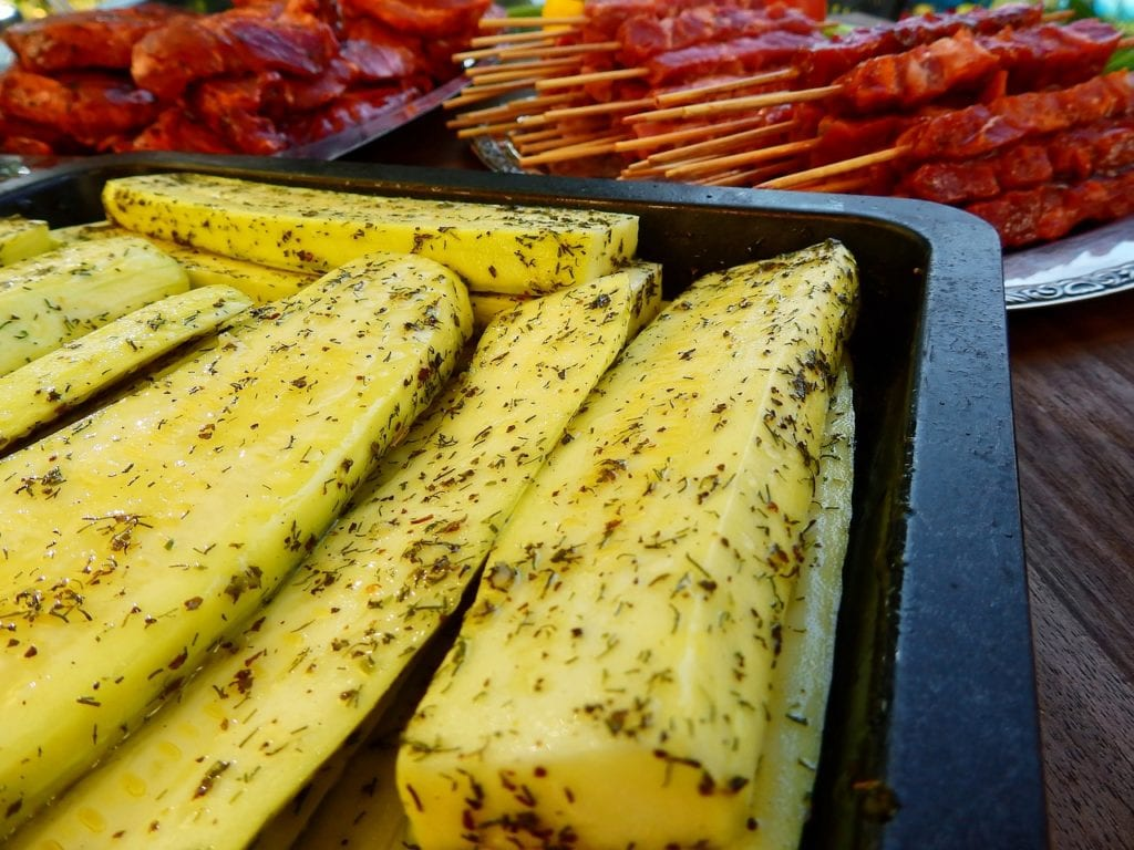 Sliced squash seasoned prepped to grill.