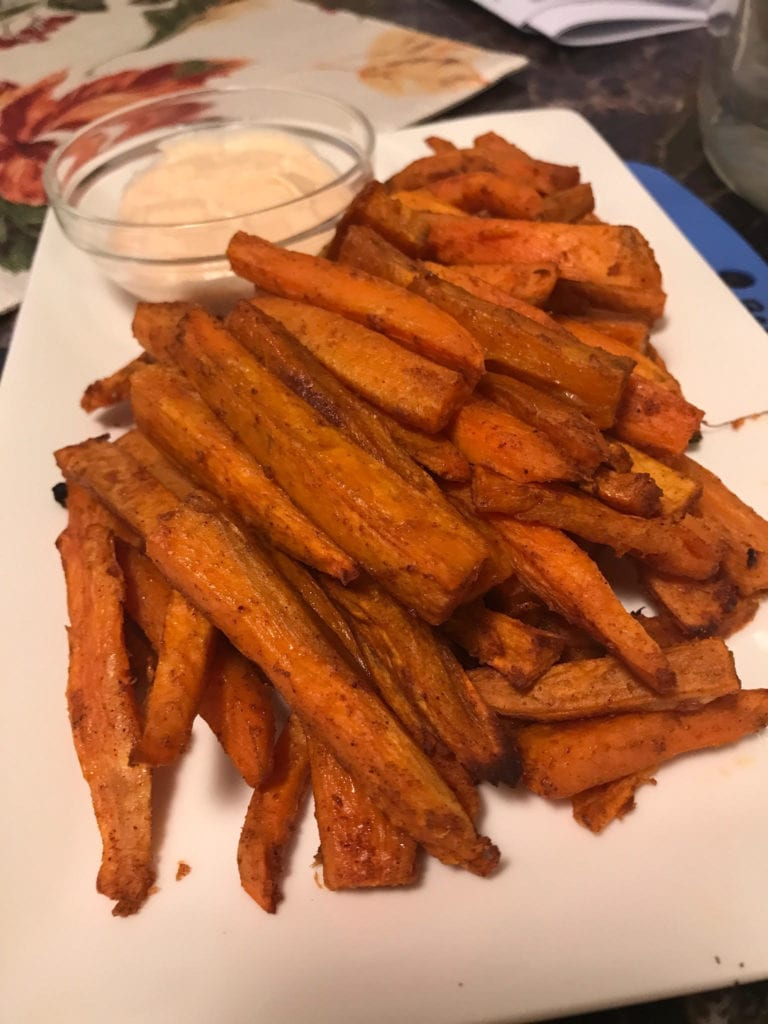 Sweet potato fries layered on a white rectangular serving plate with dipping sauce.