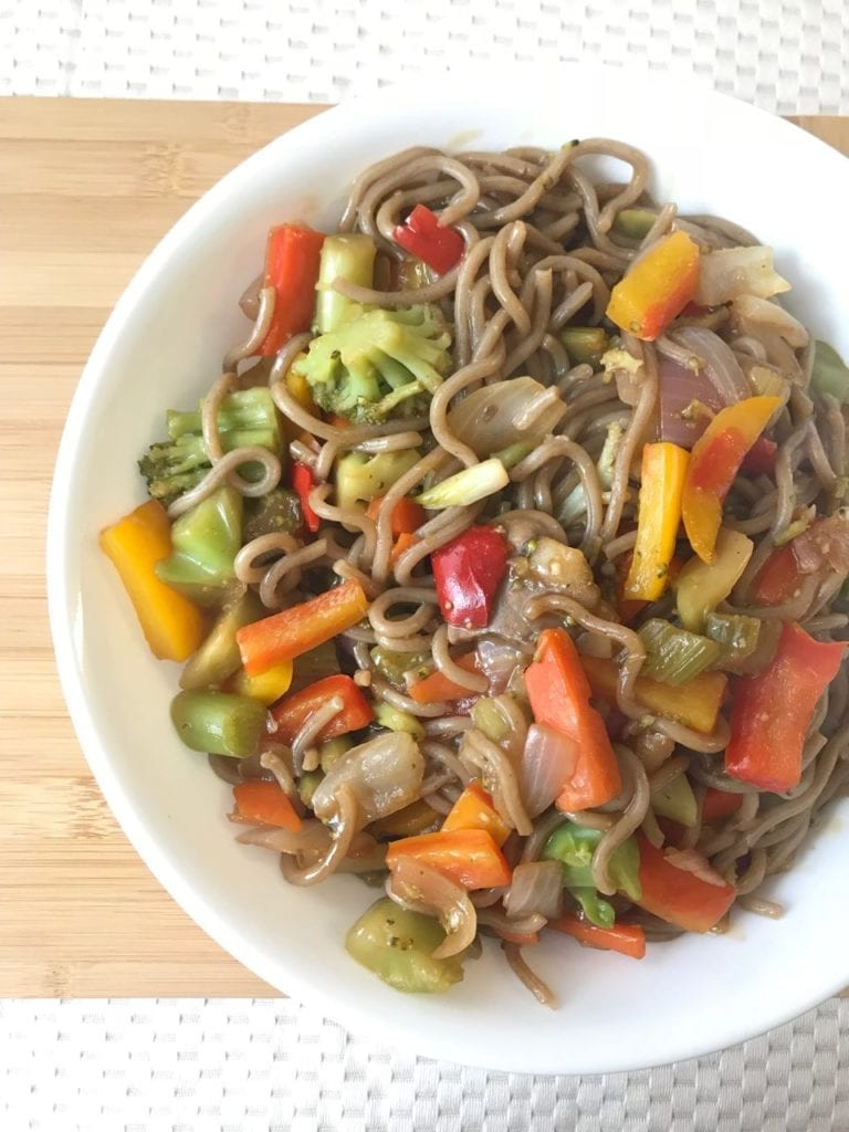 Bowl of vegetable stir fry on a cutting board