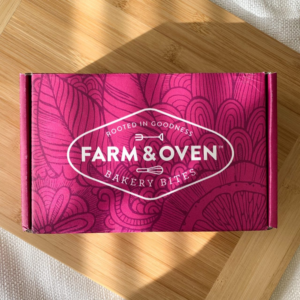 "Pink box on a wooden cutting board that says ""Farm and Oven"""