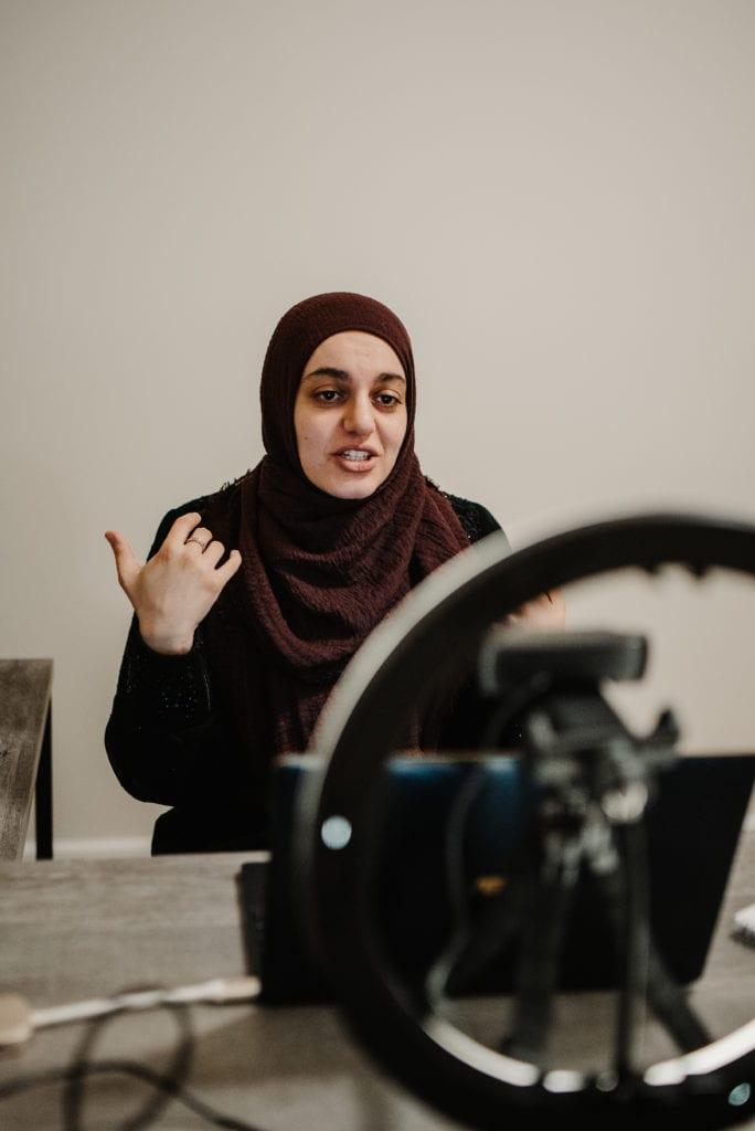 Dua recording her webinar series on a laptop