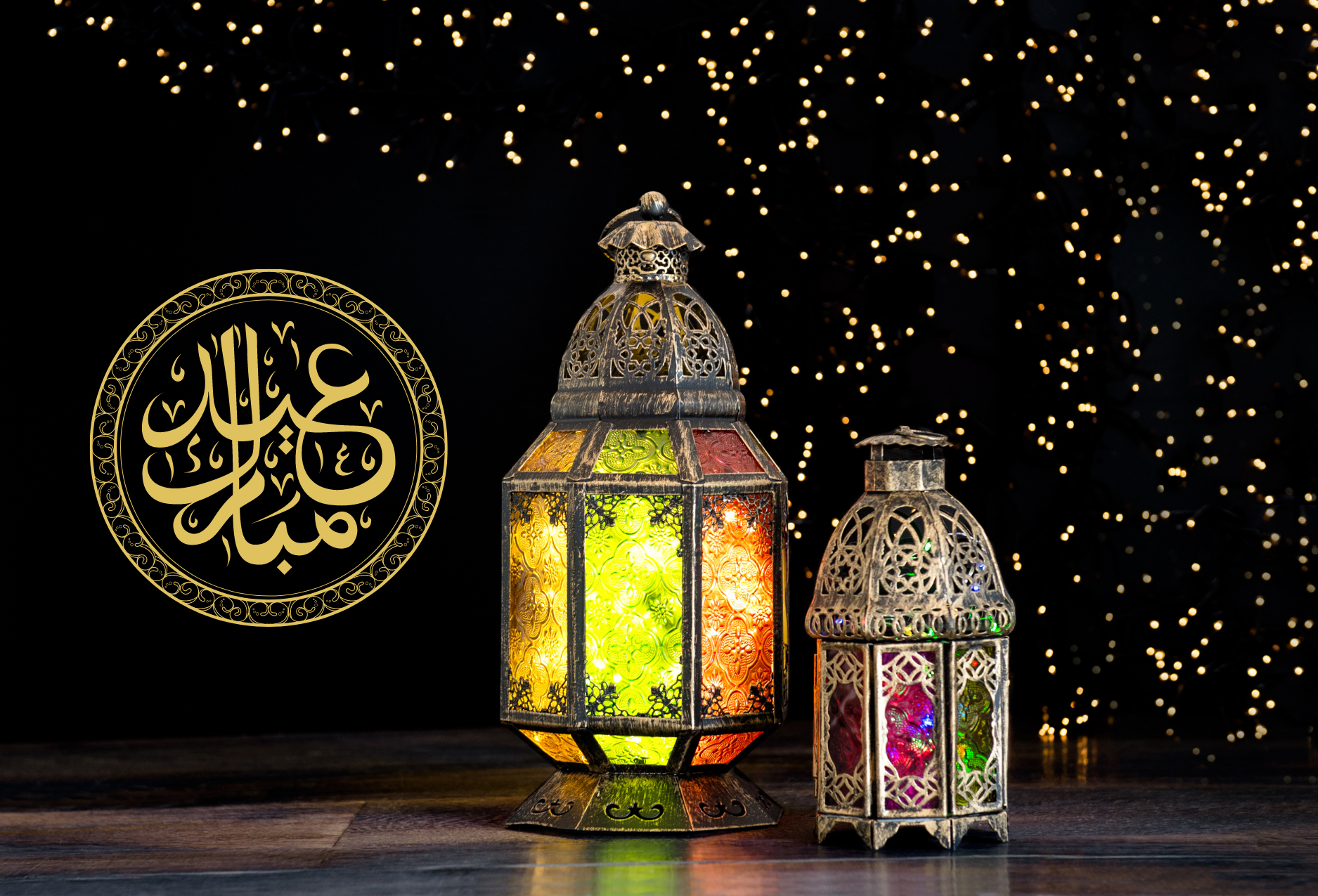 Learn about Eid. A starry black backdrop with two Eid/Muslim lanterns and arabic calligraphy reading Eid Mubarak.